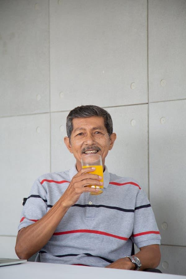 Zumo de naranja de la bebida del viejo hombre para sano en su sitio de trabajo imagenes de archivo