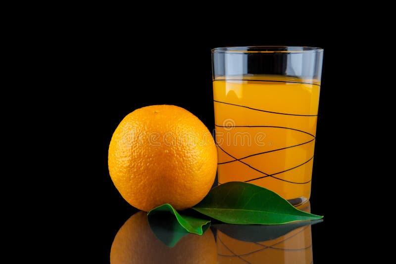 Zumo de naranja - vidrio con las naranjas en fondo negro fotografía de archivo libre de regalías
