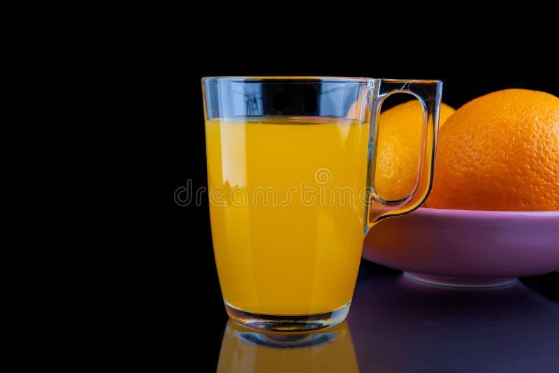 Zumo de naranja - vidrio con las naranjas en fondo negro imagenes de archivo
