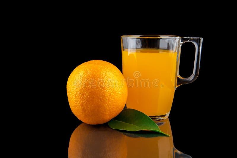 Zumo de naranja - vidrio con las naranjas en fondo negro imágenes de archivo libres de regalías
