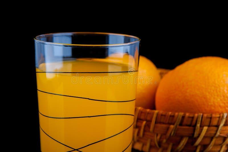 Zumo de naranja - vidrio con las naranjas en fondo negro foto de archivo