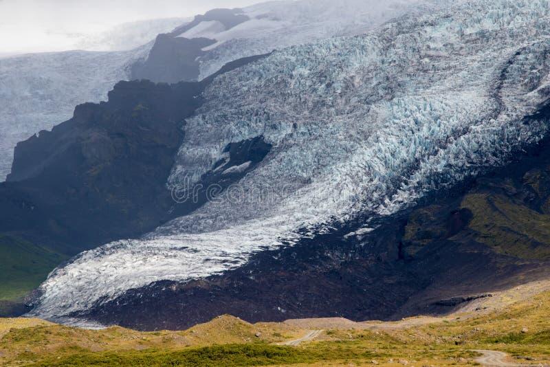 Zunge des Gletschers in Island, das unten vom grünen Moosberg am nebeligen Tag treibt Blaues Gletschereis ist sichtbar lizenzfreies stockbild