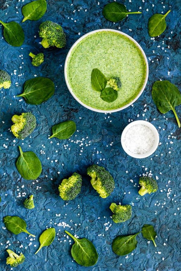 Zupa ze śmietany z brokułów i szpinaku na niebieskim biurku Wzorzec roślinny obrazy royalty free