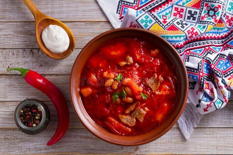 Zupny borscht robić z warzywami, mięso, fasole i burak, zakorzeniamy w pucharze na drewnianym stole obraz stock