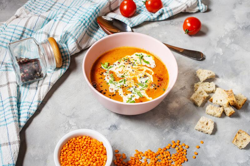 Zuppa di lenticchie deliziose con panna pesante sul tavolo di calcestruzzo con pepe rosso e pane tostato fotografia stock libera da diritti