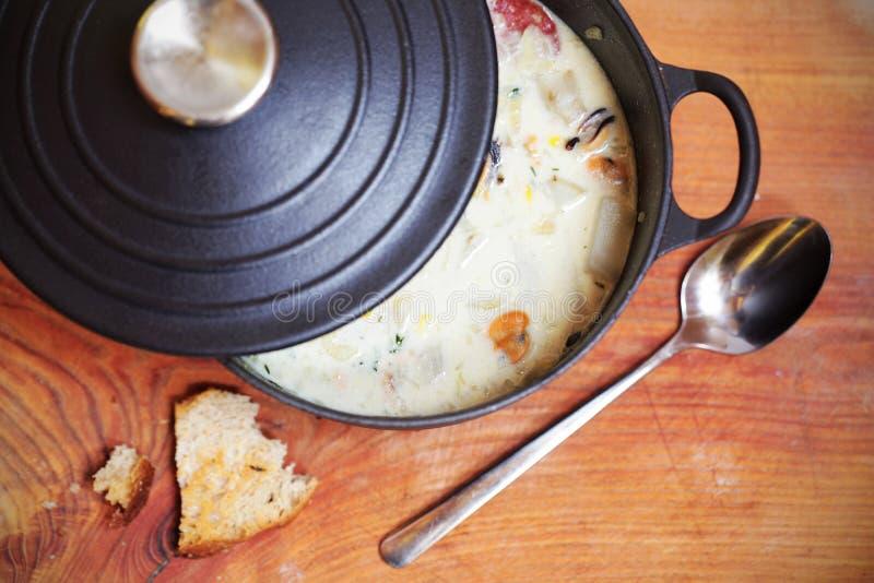 Zuppa di molluschi e latte con la salsiccia e le patate nella casseruola del ferro immagine stock