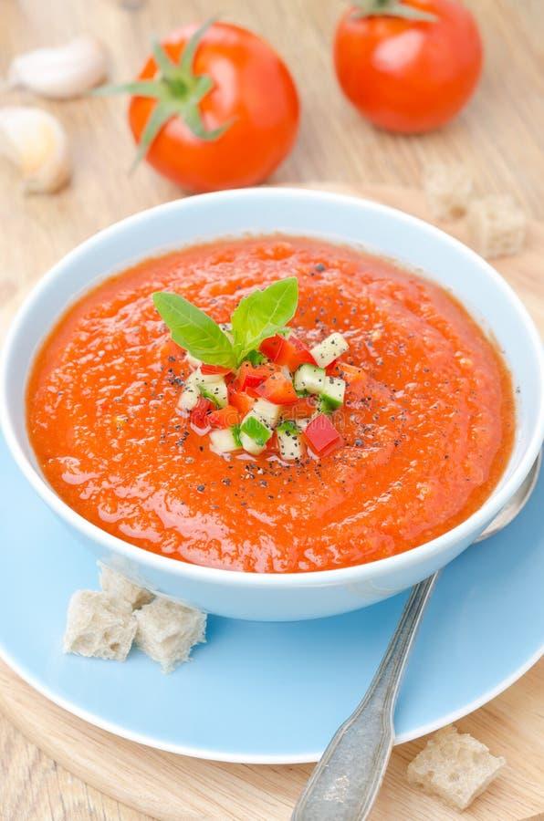 Zuppa di verdure fredda fredda della minestra del pomodoro con basilico in un verticale di vista superiore della ciotola fotografia stock