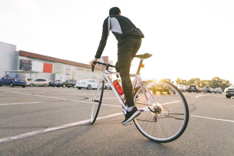 Zurück von den Fahrten eines Radfahrers auf ein weißes Landstraßenfahrrad auf Autoparken, Sonnenuntergang und moderner Architektu stockbild