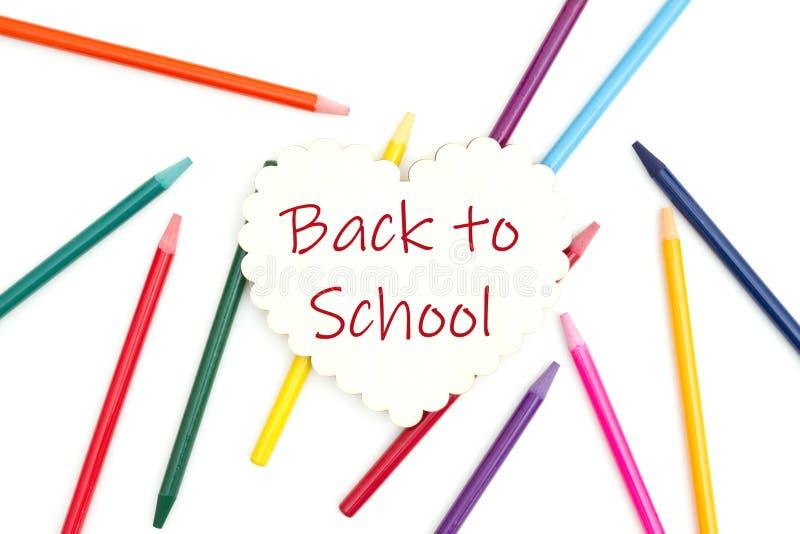 Zurück zu Schulmitteilung auf hölzernem Herzen mit farbigen Aquarellbleistiften lizenzfreies stockbild