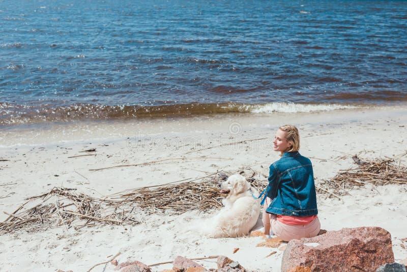 zurück Ansicht der Frau sitzend auf Ufer mit golden retriever-Hund nahe dem Meer lizenzfreie stockfotografie