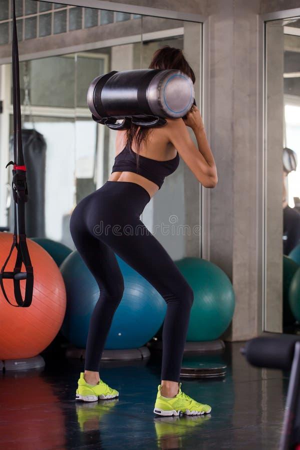 zurück Ansicht der Sportfrau in der Sportkleidungsübungshocke mit Ausbildungsanhebender Gewichtstasche in der Eignungsturnhalle T lizenzfreies stockbild