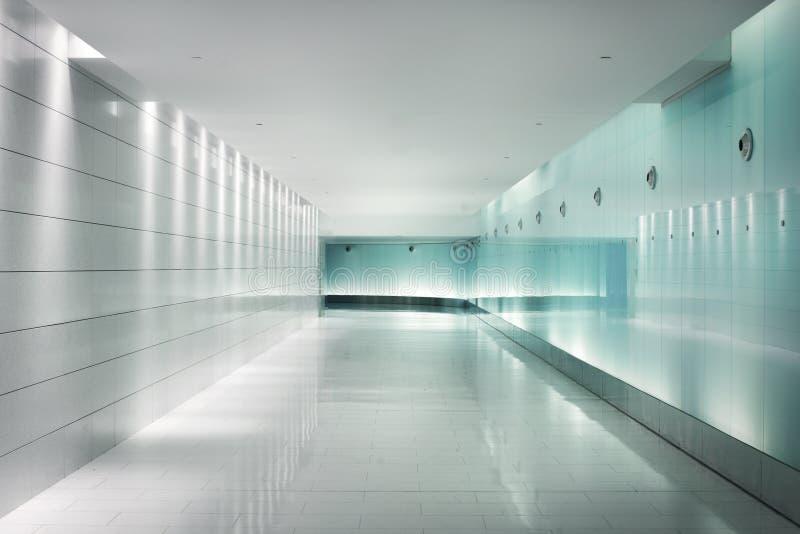 Zurück-beleuchtete Glaswände in einem untertägigen futuristischen Korridor stockfoto