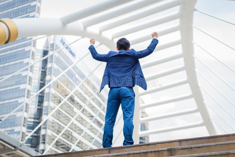 Zurück vom asiatischen Geschäftsmannstand und Hände oben von anheben feierte seins, das in der Karriere und im Auftrag erfolgreic lizenzfreie stockfotos
