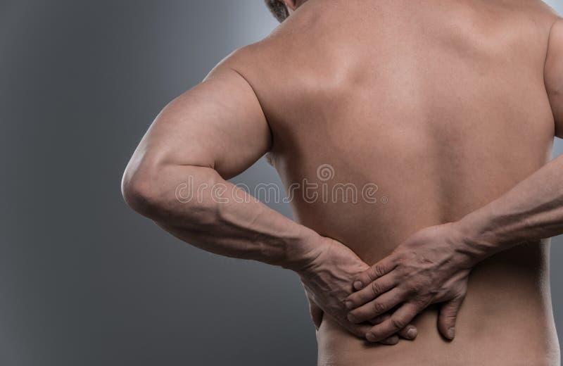 Zurück vom jungen hemdlosen Mann mit Rückenschmerzen lizenzfreie stockbilder