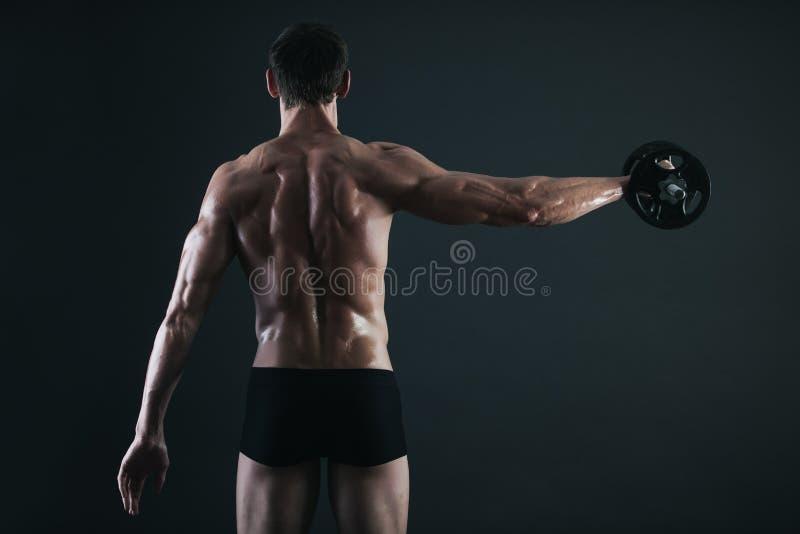 Zurück vom jungen männlichen Bodybuilder, der Gewichtsübung tut stockbild