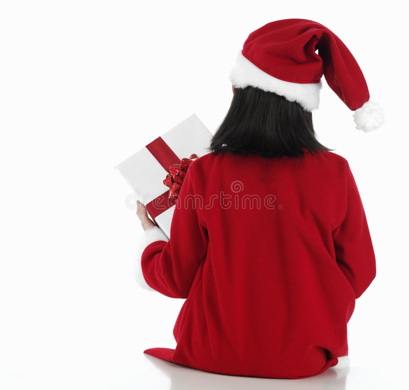 Zurück vom Weihnachtskleinen Mädchen mit sehr großem Geschenk stockfotografie