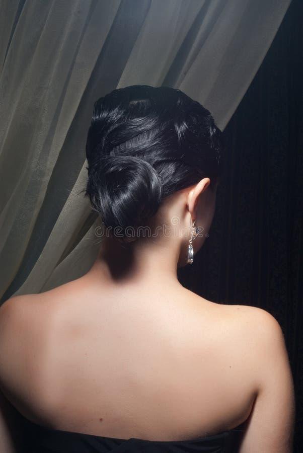 Zurück von der Brunettefrau mit Frisur lizenzfreie stockfotografie