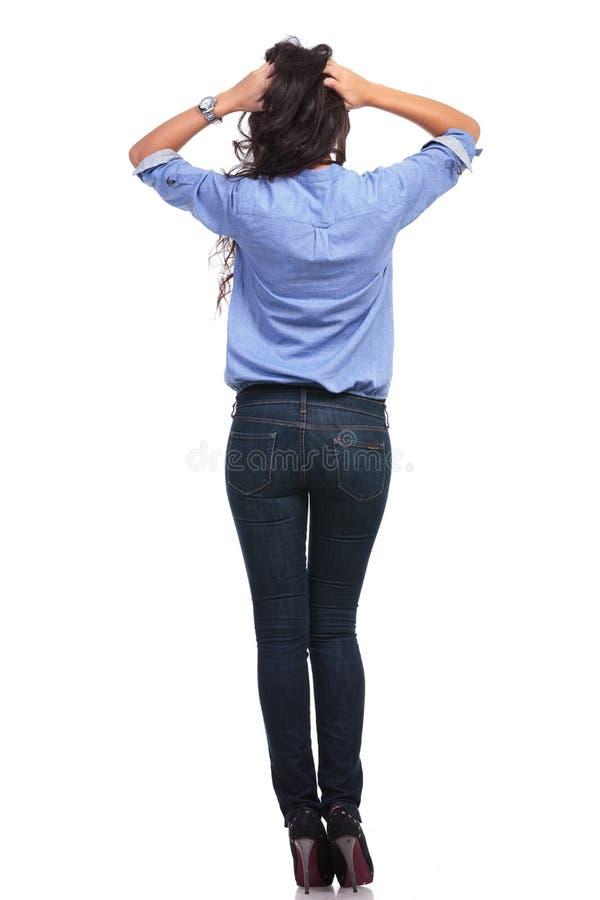 Zurück von der zufälligen Frau mit den Händen im Haar lizenzfreie stockfotografie