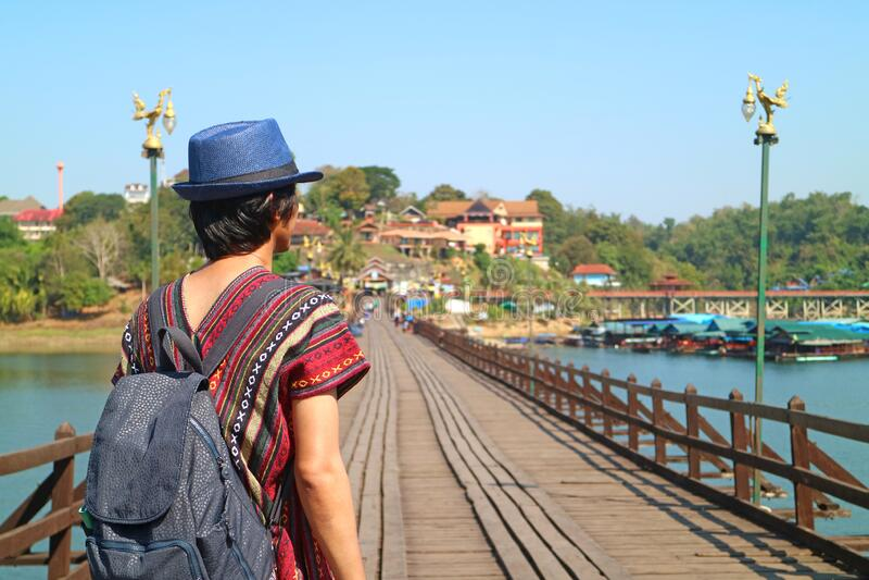 Zurück von einem Reisenden mit Blurry Mon Bridge, das Ikonische Wahrzeichen von Sangkhlaburi, Thailand im Hintergrund stockbilder