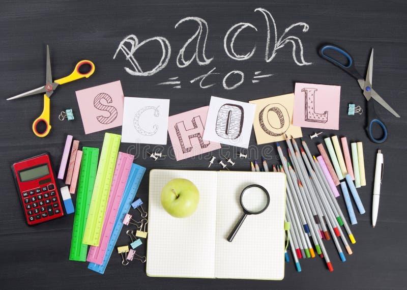 ` Zurück zu dem Schule-` handgeschrieben mit Schulbedarf auf einem schwarzen Hintergrund Beschneidungspfad eingeschlossen stockbilder