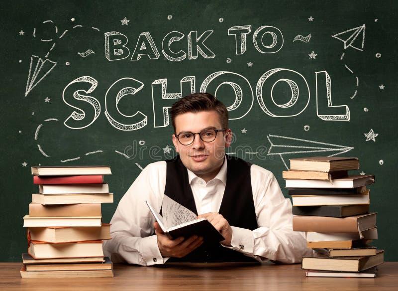 Zurück zu dem Schullehrer, der am Klassenzimmerschreibtisch sitzt lizenzfreie stockfotografie