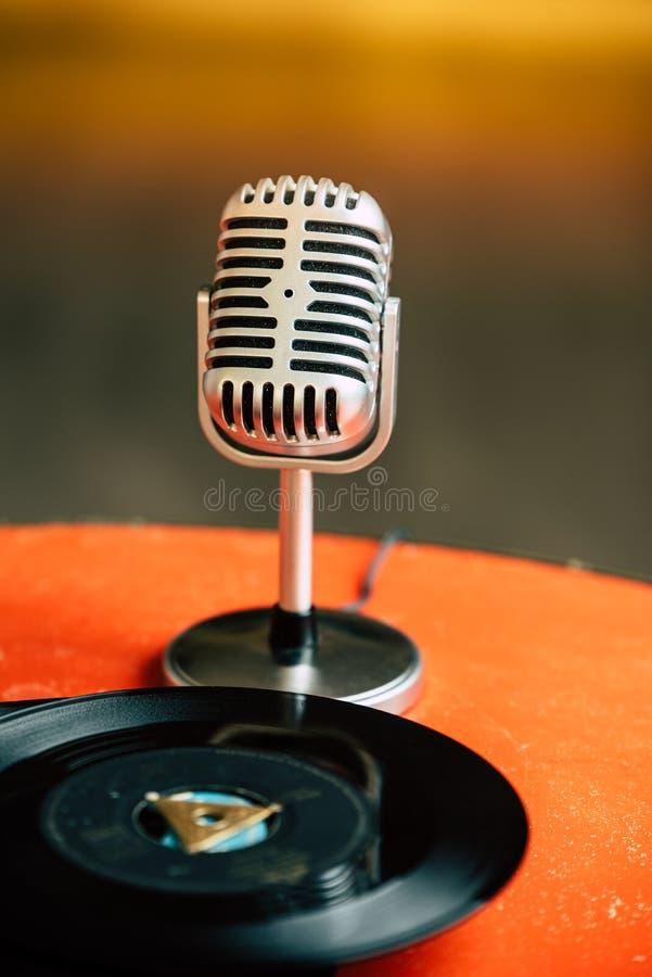 Zurück zu 50s - nostalgisches Bild eines fünfziger Jahre Mikrofons, das auf einer alten orange Tabelle mit alten Vinylaufzeichnun stockbild