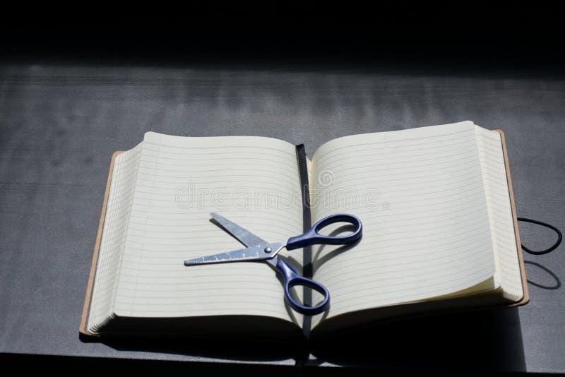 Zurück zu Schulanmerkungsblock Scissors Notizbuch blaues Stahlmetallsilber stockfoto