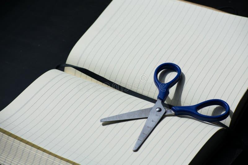 Zurück zu Schulanmerkungsblock Scissors Notizbuch blaues Stahlmetallsilber stockbild