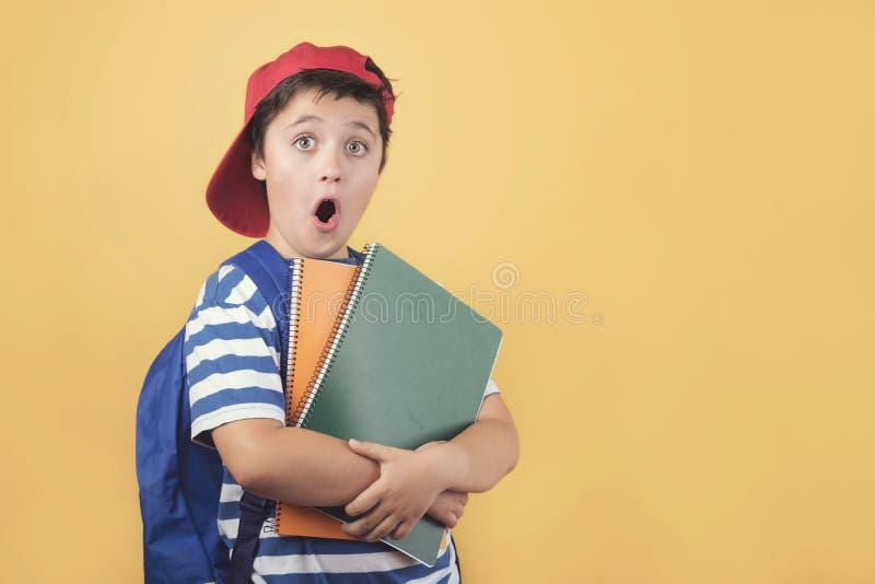 Zurück zu Schule, überraschtem Kind mit Rucksack und Notizbuch stockbilder