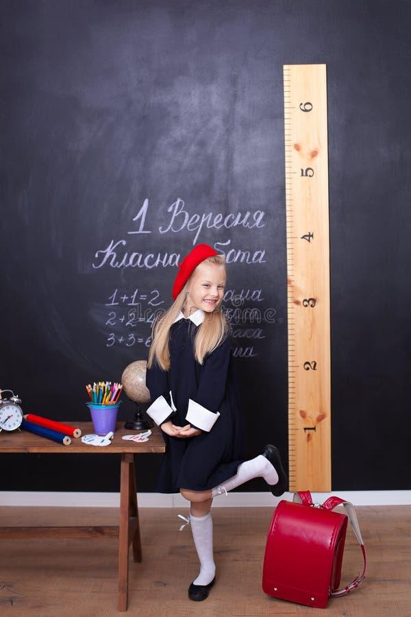 Zurück zu Schule! Das Mädchen steht in der Schule nahe dem Brett Auf schwarzem Hintergrund mit copyspace Schulmädchenantworten an stockfoto