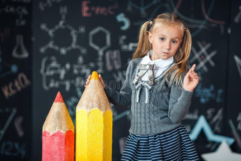 Zurück zu Schule! Ein kleines blondes Mädchen in den Schuluniformständen mit zwei sehr großen Bleistiften auf dem floore gegen Ta lizenzfreies stockfoto