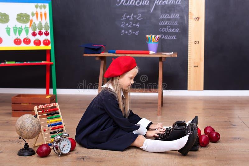 Zurück zu Schule! Ein Mädchen sitzt auf dem Boden in der Schule und hält eine Retro- Schreibmaschine Schulbildung Auf der Tafel i lizenzfreie stockfotos