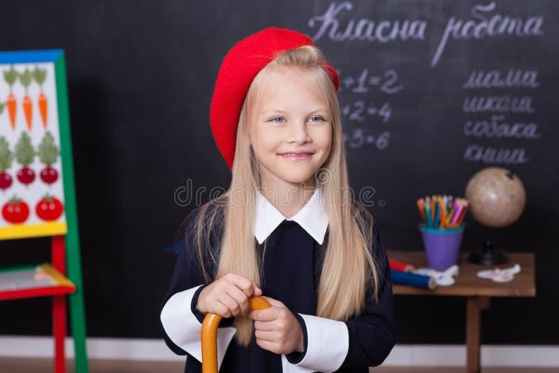 Zurück zu Schule! Ein Schulmädchen steht an der Tafel mit einem Machthaber Ein Schulmädchen beantwortet die Lektion Ein Erstsorti lizenzfreies stockfoto