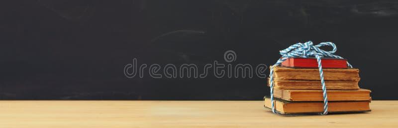 Zurück zu Schule-Konzept Stapel Bücher über hölzernem Schreibtisch vor Tafel lizenzfreie stockbilder
