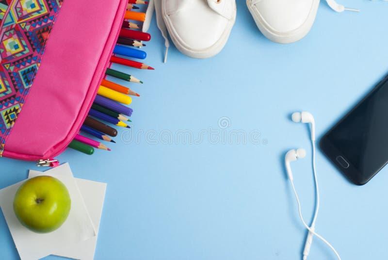 Zurück zu Schule, rosa Fall, Mittagessensandwichapfel, bunten Bleistiften und blauem Hintergrund mit Kopienraum stockfoto