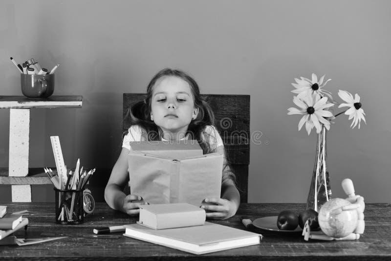 Zurück zu Schule und Kindheitskonzept Schulmädchen sitzt am Schreibtisch mit buntem Briefpapier, Büchern und Blumen stockfoto