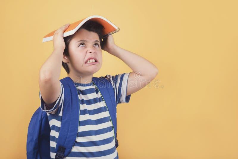 Zurück zu Schule, verärgertem Jungen mit Rucksack und Notizbuch stockfotografie