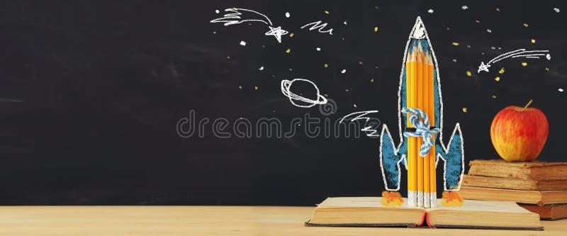 Zurück zu Schulefahne schnellen Sie Skizze und Bleistifte über offenem Buch vor Klassenzimmertafel hoch lizenzfreie stockfotografie