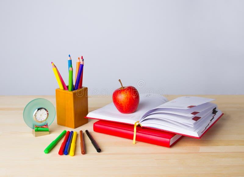 Zurück zu Schulhintergrund mit Büchern, Bleistiften und Apfel über Holztisch stockbild