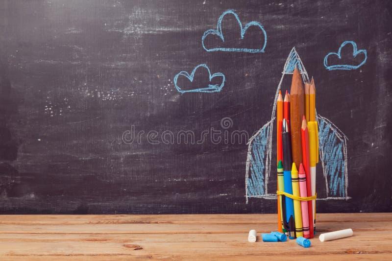 Zurück zu Schulhintergrund mit der Rakete hergestellt von farbigen Bleistiften stockbild