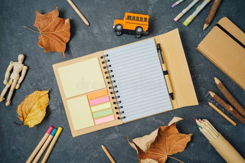 Zurück zu Schulhintergrund mit Notizbuch, Schulbedarf und Herbstlaub auf Tafel stockfoto