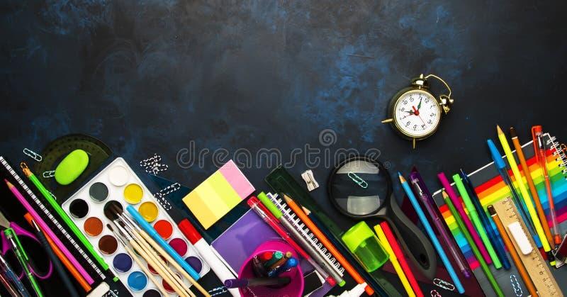 Zurück zu Schulhintergrund mit Raum für Text, Notizbücher, Stifte, Bleistifte, anderes Briefpapier auf blauem Kreidebrettschreibt lizenzfreie stockfotos