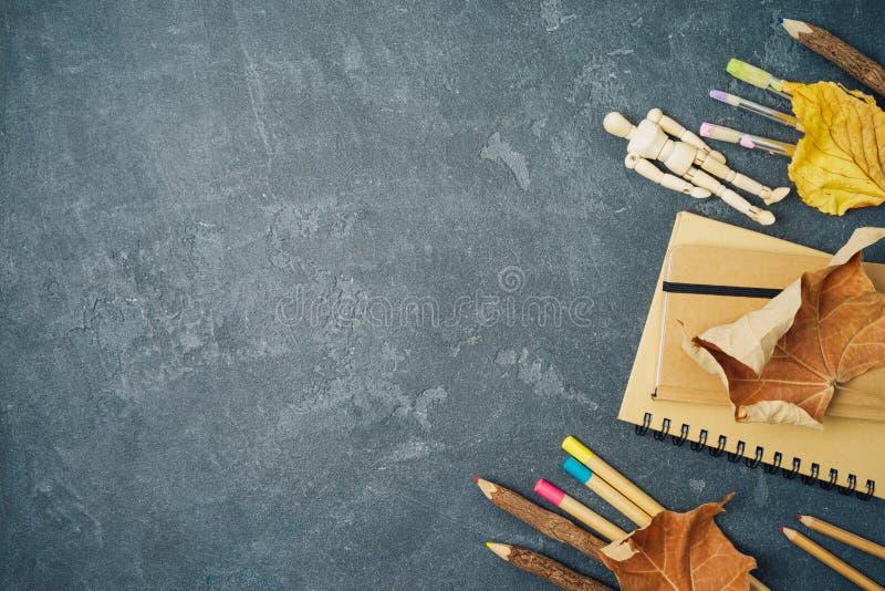 Zurück zu Schulhintergrund mit Schulbedarf und Herbstlaub auf Tafel lizenzfreie stockfotos