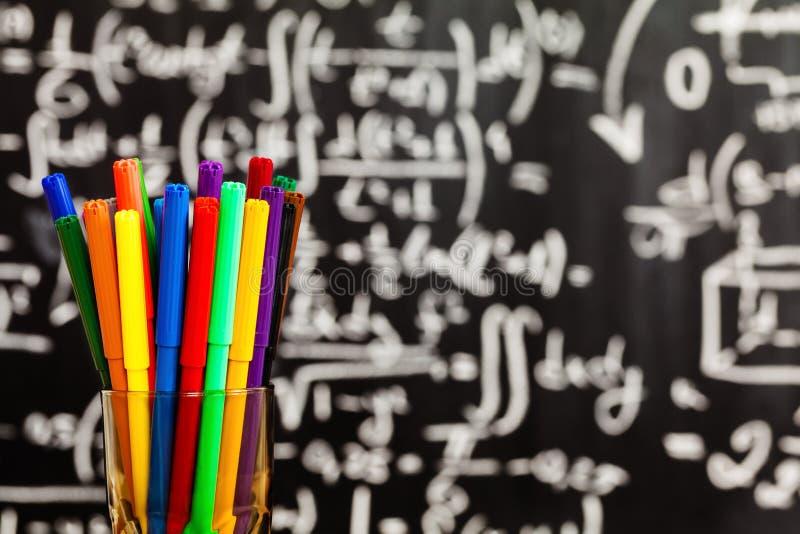 Zurück zu Schulhintergrund mit Schulbus und Schule werden durch bunte Kreiden auf die schwarze Schultafel geschrieben stockfotografie