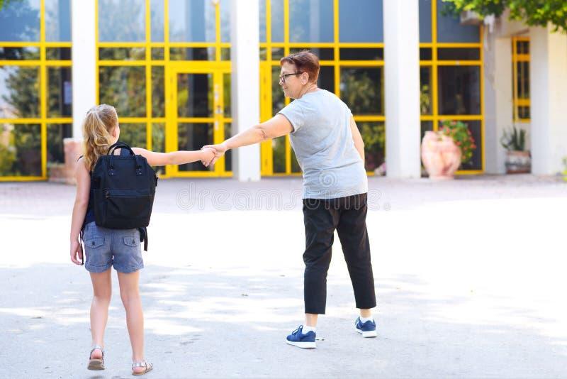 Zurück zu Schulkampf nach Sommerferien Großmutter, die ein besorgtes Kind zur Schule schleppt lizenzfreies stockfoto