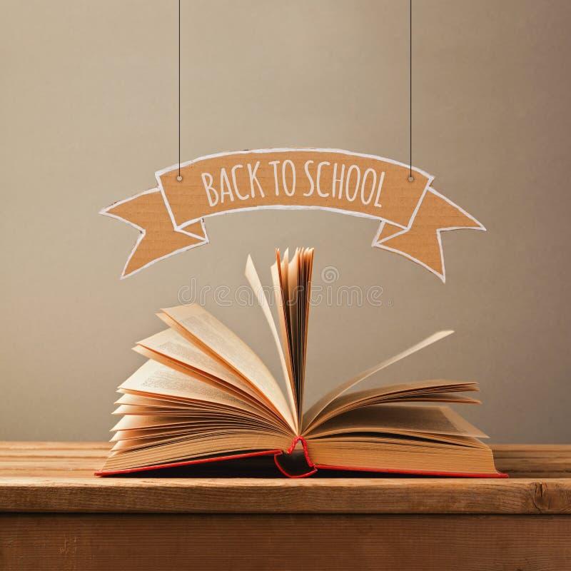 Zurück zu Schulkonzept mit offenem Buch und Fahne Öffnen Sie Buch auf hölzerner Tabelle stockfoto