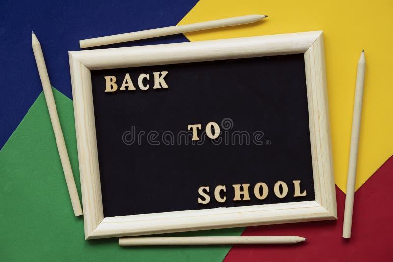 Zurück zu Schultext und hölzernen Bleistiften auf schwarzer Tafel im Holzrahmen Konzept der Ausbildung, Schule beginnend lizenzfreie stockbilder