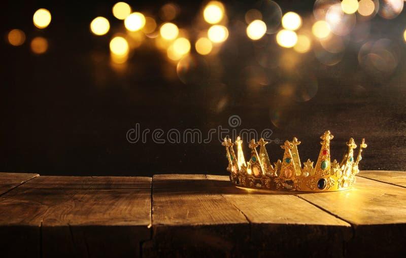 zurückhaltend von der Königin/von Königkrone über Holztisch Weinlese gefiltert mittelalterlicher Zeitraum der Fantasie lizenzfreies stockfoto