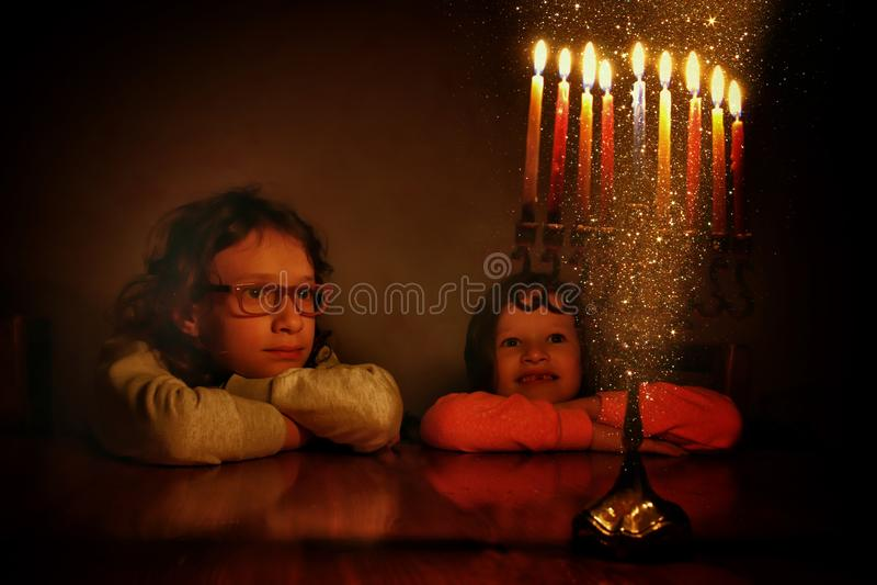 Zurückhaltendes Bild jüdischen Feiertag Chanukka-Hintergrundes mit zwei netten Kindern, die menorah traditionelle Kandelaber betr lizenzfreie stockfotografie