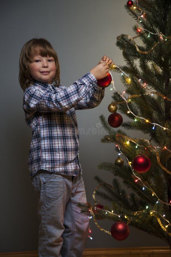 Zurückhaltendes Porträt des glücklichen Jungen Weihnachtsbaum verzierend stockfotografie